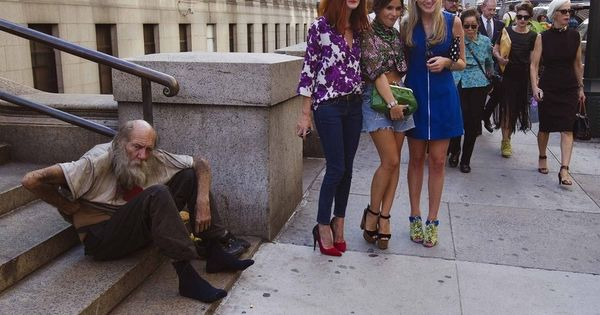 Fashionistas pose for photographs in front of a homeless man outside Moynihan