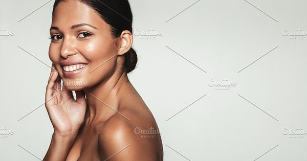 Portrait of beautiful female model with clean skin. Close up of smiling woman with healthy skin posing against grey background with copy space.