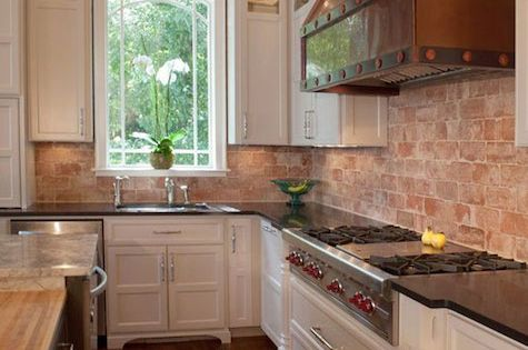 two-tone kitchen cabinets & counters; exposed brick walls; copper range hood