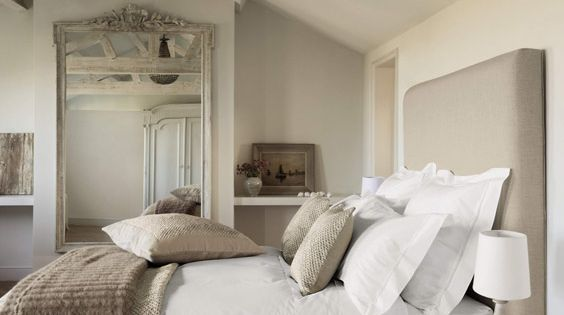 A beautiful light and airy bedroom decorated in neutral tones, with exposed