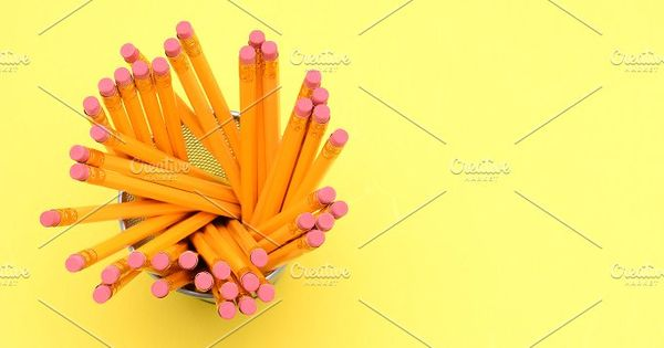 Looking down on a pencil cup filled with new pencils. On a bright yellow background with the eraser end towards the camera. Horizontal Format with copy space.