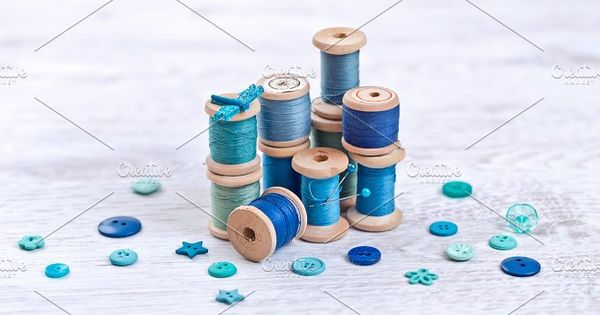 Collection of spools threads in gree, blue, aqua colors arranged on a white wooden table