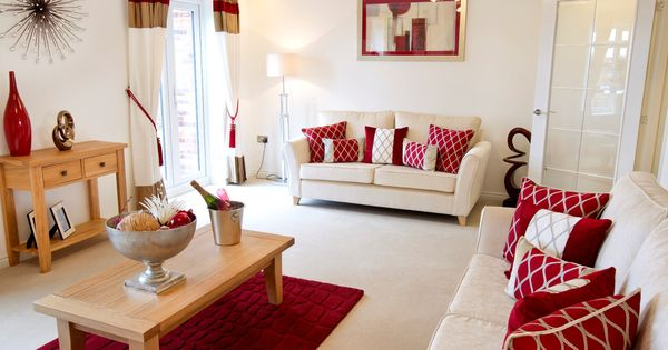 Red hues complement the welcoming cream interior of this for Brown and cream living room ideas