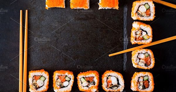 Traditional Japanese food – sushi, rolls and chopsticks for sushi on a dark background