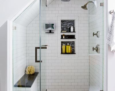 A crisp black-and-white-tiled shower, tucked under attic eaves, feels spacious