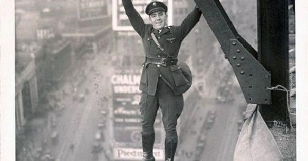 A 50's police officer hanging from a steel beam above Times Square.