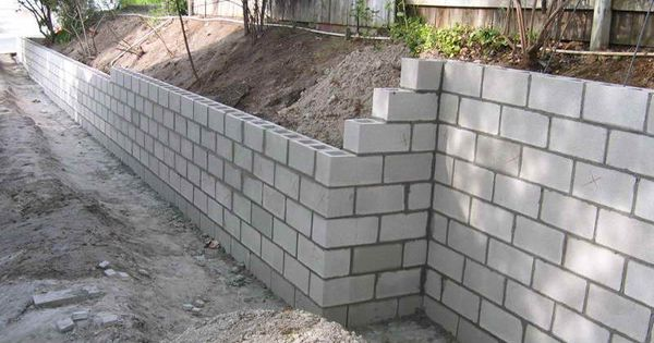 Cinder block retaining wall leave it plain so the kids Cinder block retaining wall