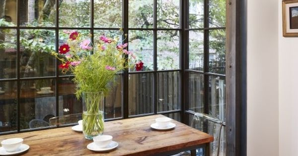 Windows in the dining room area. Rustic table with clear chairs.