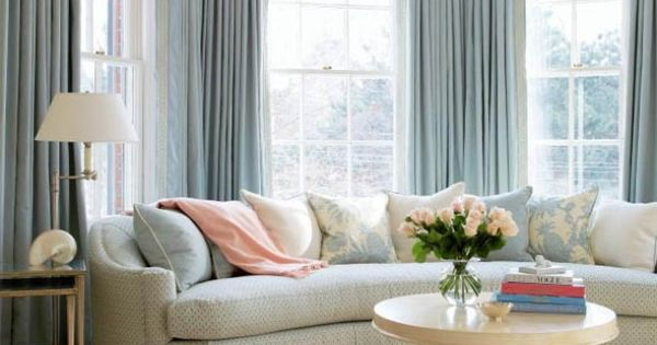 Double Sets Of Pinch Pleat Curtains With A Curved Sofa