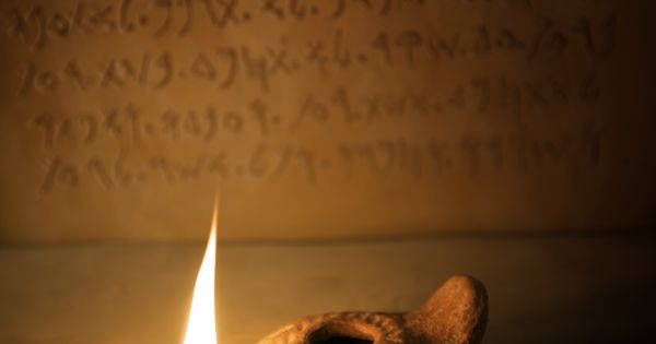 Lit Oil Lamp In Front Of Ancient Hebrew Text Archeology