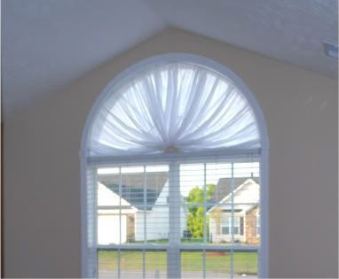 Half Moon Window Treatments Covering A Large Bedroom Window