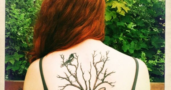 Back tattoo of deer in business suit with tree branches as antlers