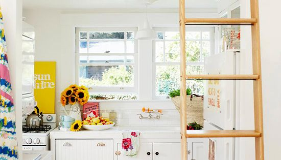 White kitchen with bright accents; ladder to loft.