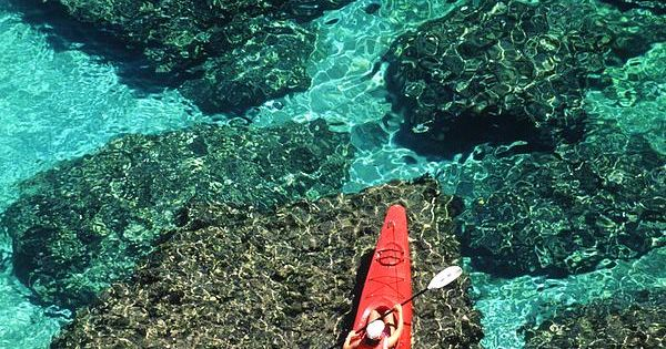 To Kayak against crystal clear waters. Kayakers in clear blue water off