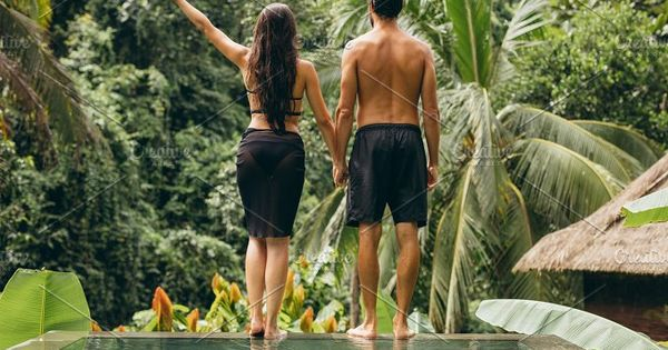 Rear view shot of young couple standing on the edge of the pool holding hands and looking at a view. Man and woman at luxury holiday resort.