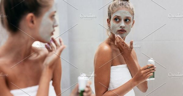 Young woman applying mask cream on face in bathroom. Female in doing beauty treatment on her face skin in front of mirror after bath.