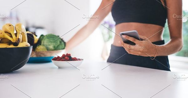 Cropped shot of young woman with mobile phone in kitchen. Fruits and vegetable on kitchen counter.