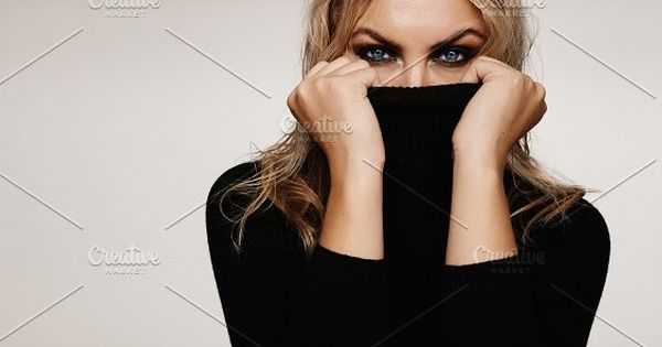 Beautiful young woman covering her face with focus on her eyes