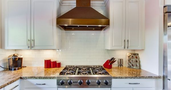White Glass Subway Tile Backsplash With White Cabinets And