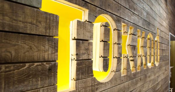 TOKKAD | type routed out of wood planks, lit with neon color