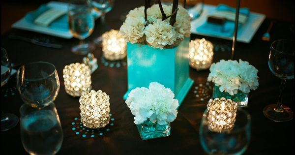 Light aqua or Tiffany blue centerpiece with white carnations, candles, and branches
