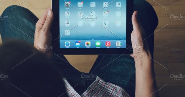 Apple ipad mockup. Man sitting down using an apple ipad overhead view. Man is wearing checked shirt and blue jeans. Wooden flooring.