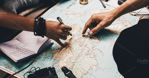 Close up view of man and woman pointing at places on world map. Woman noting vacation plan in a diary.