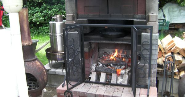 Outdoor fireplace with cooking shelf cooking pizza in cast iron ...