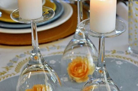 Wedding centerpiece idea: wine glass candle holder with orange flower decoration