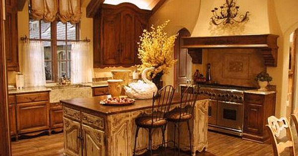 French kitchen with white island and darker wood cabinets around. Walls in