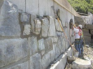 Covering Cement Blocks With Rock Facing The Best Way To Dress Up That Oh So Important Retaining Wall Backyard Backyard Landscaping Front Yard