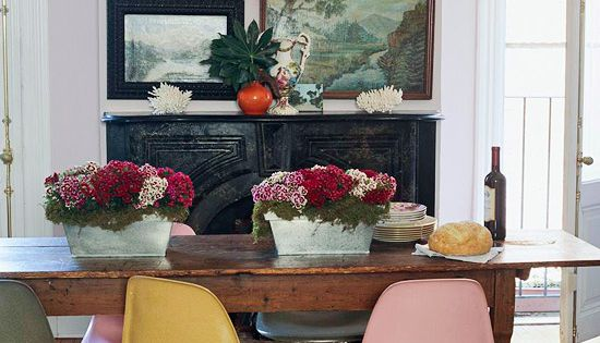 Brightly coloured eames chairs with farmhouse table and oil landscape paintings. dining
