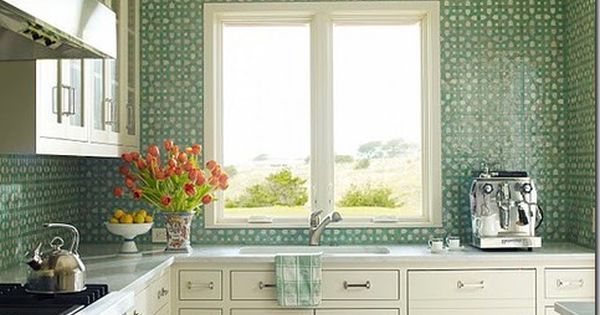 A white kitchen with aqua mosaic tiles from counter to ceiling backsplash.