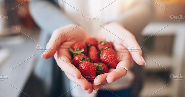 Cropped image a woman's hands holding a bunch of strawberries. Female holding a handful of fresh strawberries.