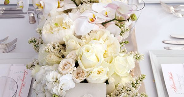 Lush white wedding centerpiece with a hint of burlap as the table