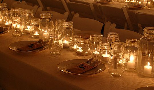 Mason jars with tea lights lining the center of a table.