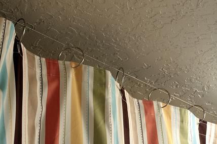 Curtain Hung From Ceiling As Room Divider To Hide The Tool Chest