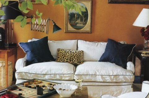 Deep orange walls, black and leopard pillows, contrast welting on the furniture,