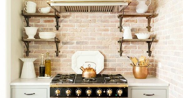 Rustic kitchen with golden accents, black stove and oven, and white decorative