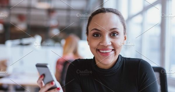 Portrait of cheerful young woman holding a mobile phone. African woman looking at camera smiling while at work.