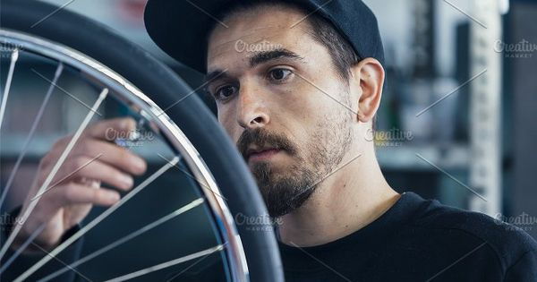 Young bearded craftsman looking at bicycle wheel