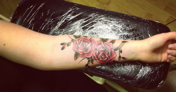 red rose tattoo on lower arm