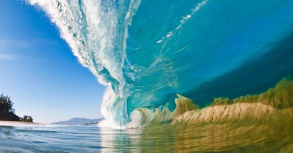 A large wave surges outward as it hits the shallow sand bank,