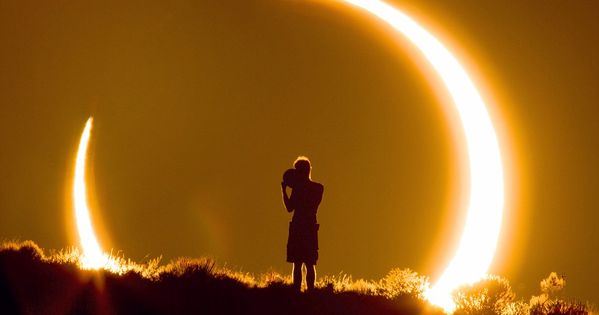 Surrounded by the sun: Stunning image shows boy watching solar eclipse... taken
