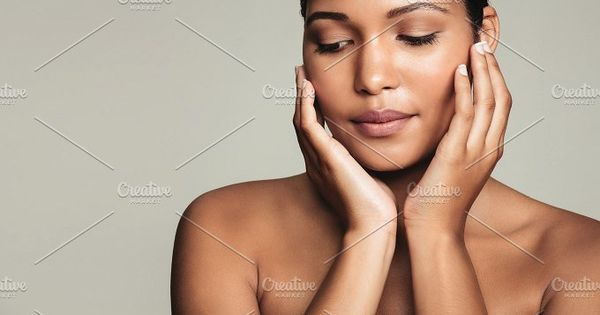 Closeup of a beautiful young woman with perfect healthy skin on grey background. Natural Beauty with fresh and clean skin.
