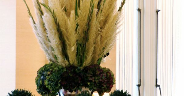 Plumes of pampas grass with gladiolus in a tall vase