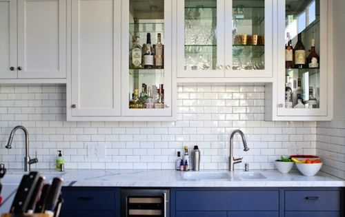 Kitchen: white subway tile, white upper cabinets, colored lowers with marble countertops.