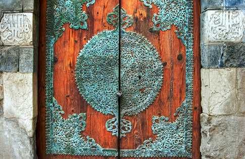 Beautiful copper (?) scrollwork decorations on heavy wooden double door. India? Indonesia?