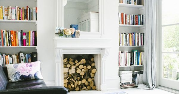 Bookshelves in alcoves on either side of fireplace in living room of