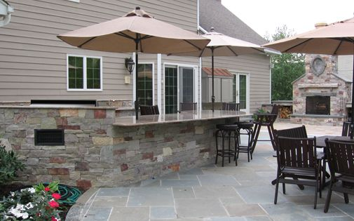 Shape of fireplace in background bbq outdoor kitchen built for Outdoor kitchen designs nj